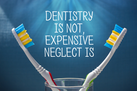 two toothbrushes on a blue background and the inscription Dentistry is an expensive neglect is. Dentistry and oral care concept Imagens