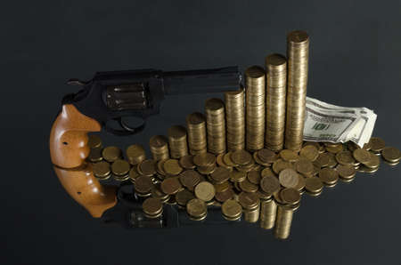 arrangement of coins and gun on grey background