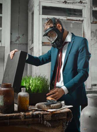 Photo d'homme en masque à gaz avec valise. Dans la valise germé le blé Banque d'images - 84436697