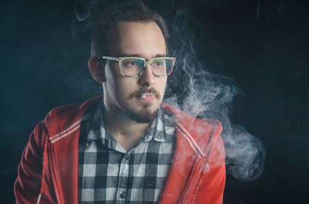 portrait of a guy in a plaid shirt with a beard. smokes electronic cigarettes. nicotine addiction Foto de archivo