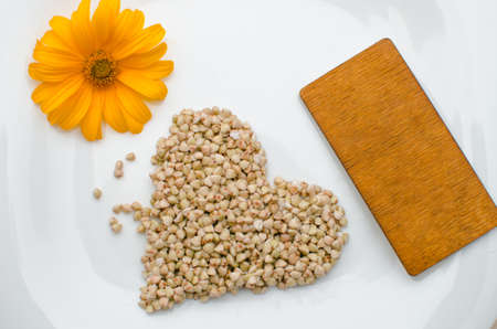 photo of germinated buckwheat on a white plate next to a green leaf and a yellow flower Banque d'images