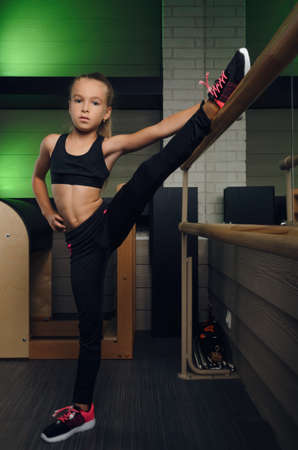 Schoolgirl trains in the gym Pilates in the fitness club