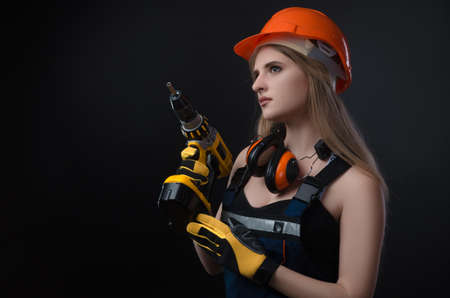 girl in construction clothes and protective equipment posing with a screwdriver