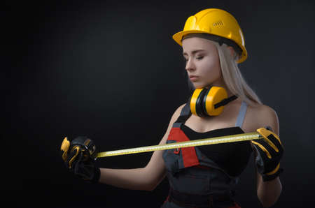 girl in a construction firm works with a tape measure