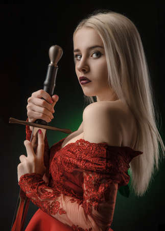 beautiful girl in red dress with sword Foto de archivo - 116849909