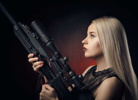 young blonde girl in black dress posing on black background with weapon 版權商用圖片