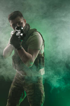 the man in military special clothes posing with a gun in his hands on a dark background in the haze