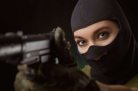 the girl in military special clothes posing with a gun in his hands on a dark background in the haze