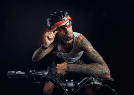 guy in a Bicycle helmet emotionally posing on a black background Reklamní fotografie