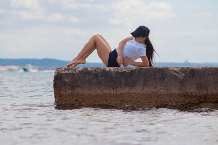 beautiful slender girl lying on the pier by the sea