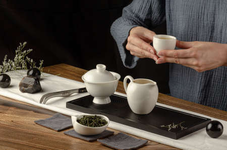 tea table with instruments teapots cups pancake and tea Shen Puer Imagens