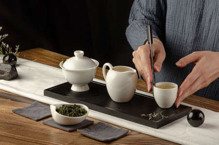 tea table with instruments teapots cups pancake and tea Shen Puer