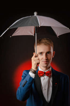 a young man, the magician, the magician holds the umbrella