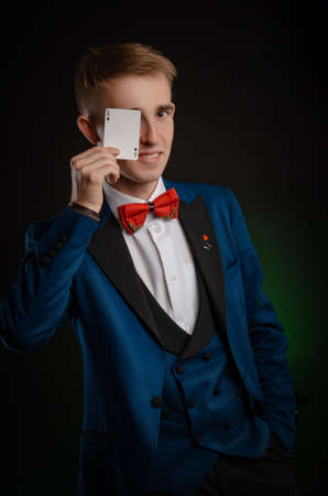 a young magician guy is holding cards in his hands