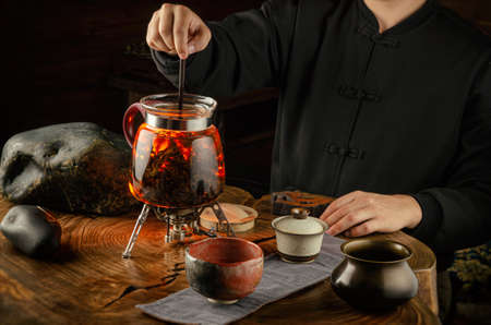 tea ceremony brewing tea on fire in a glass teapot Banco de Imagens