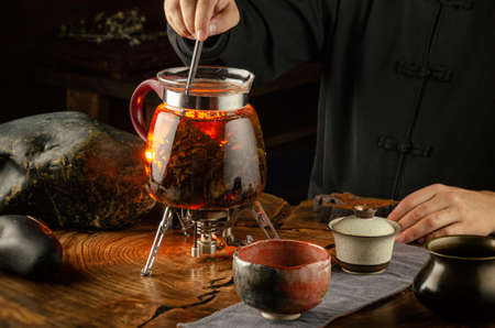 tea ceremony brewing tea on fire in a glass teapot 写真素材