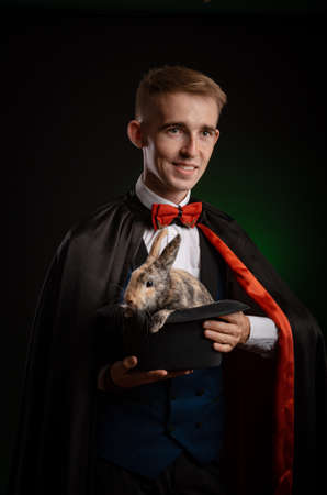 a young guy magician illusionist holding a hat with a rabbit