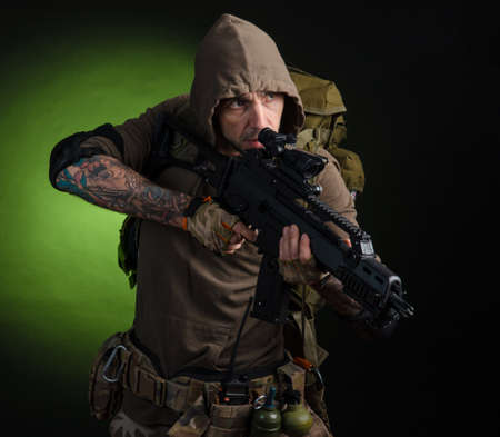 man Stalker with a gun with an optical sight and a backpack on a dark background Stock Photo