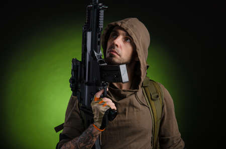 man Stalker with a gun with an optical sight and a backpack on a dark background Standard-Bild
