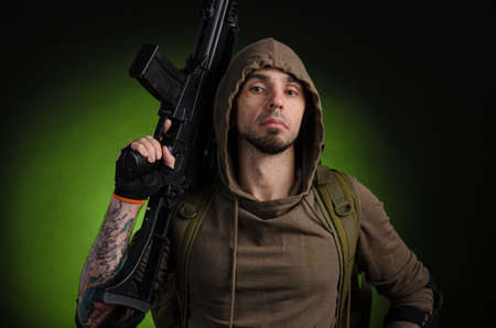 man Stalker with a gun with an optical sight and a backpack on a dark background