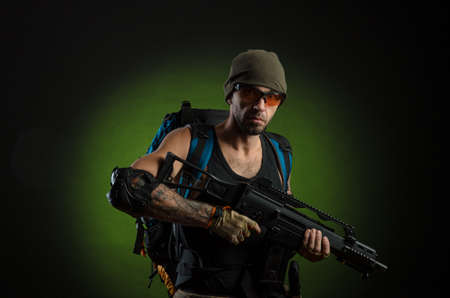 man with gun and backpack on dark background Banco de Imagens