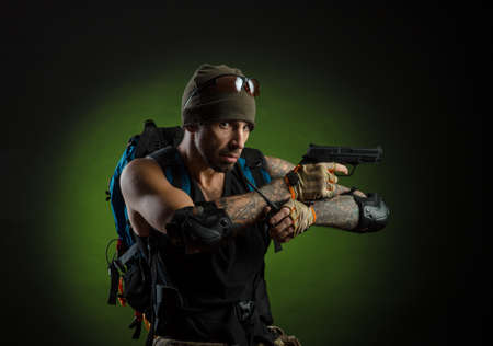 man with gun and backpack on dark background