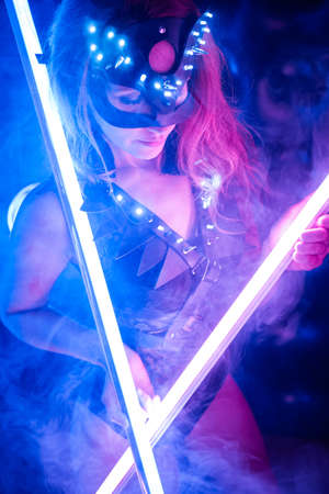 A girl in a sexy cat and party costume posing in a neon set for Halloween