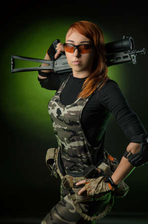 the girl in military airsoft clothes poses with a gun in her hands on a dark background
