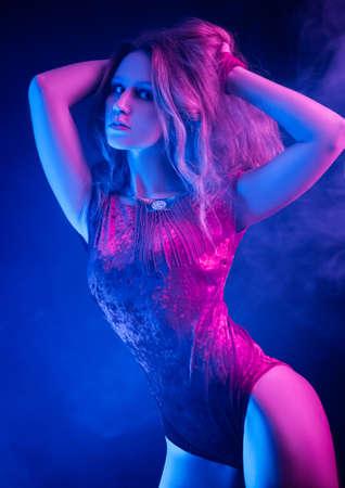 the beautiful stylish fashionable girl in bodysuit posing in photo Studio on dark background in neon light