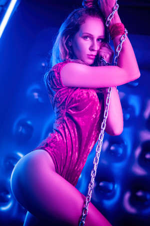the beautiful stylish fashionable girl in bodysuit posing in photo Studio on dark background with chains in neon light Stockfoto