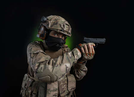 a male soldier in military clothes with a weapon pistol on a dark background