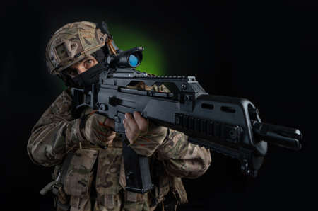 a male soldier in military clothes with a weapon on a dark background Imagens