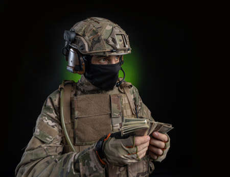 a male soldier in military clothes with a weapon on a dark background Stock Photo