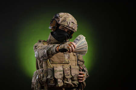 a male soldier in military clothes with a weapon on a dark background with money Stock Photo