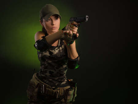 the girl in military overalls airsoft posing with a gun in his hands on a dark background in the haze Stock Photo
