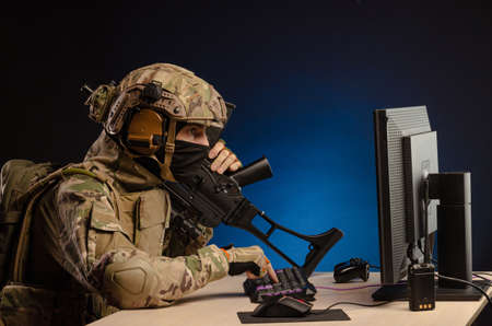 military in uniform sitting at a computer conducts cyber warfare