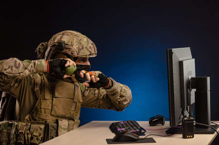 military in uniform sitting at a computer are cyberwar, playing, throwing a grenade