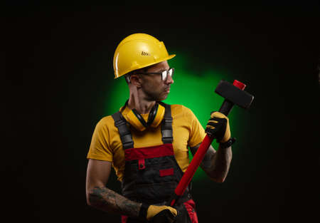 the male construction worker with a sledgehammer Imagens