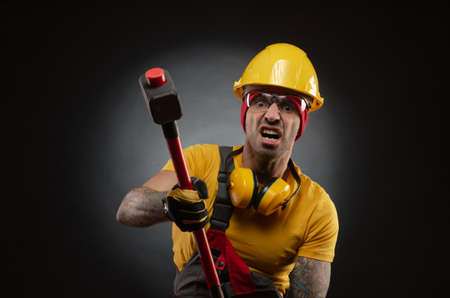 the male construction worker with a sledgehammer Banco de Imagens