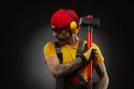 male construction worker with a sledgehammer Imagens