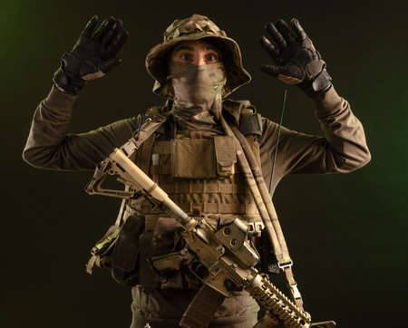 a saboteur soldier in military clothing with a weapon on a dark background surrenders with his hands up