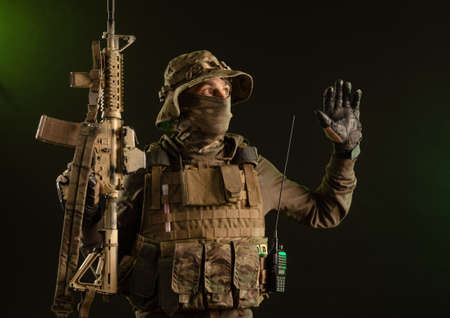 a saboteur soldier in military clothing with a weapon on a dark background surrenders with his hands up Imagens