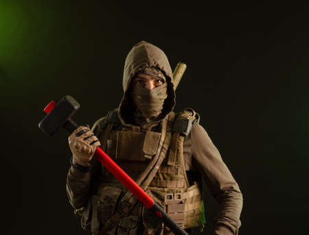 a soldier-saboteur rebel in military clothing with a weapon on a dark background holding a sledgehammer