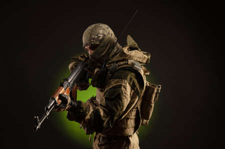 soldier militia saboteur in military clothing with a rifle on a dark background