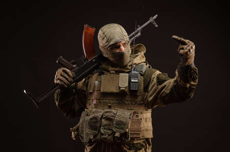 a saboteur soldier in military clothing with a weapon on a dark background shows gestures