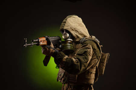 soldier Stalker saboteur in military uniform with a rifle on a dark background in a gas mask