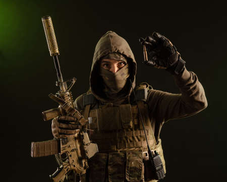 a soldier-saboteur in military uniform with a weapon on a dark background shows a bullet