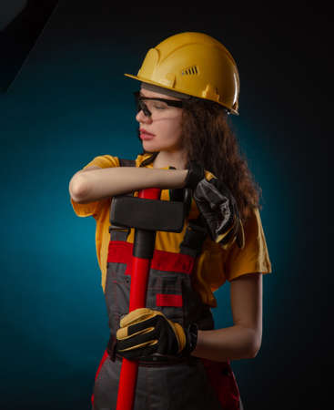 the girl in the construction helmet and overalls with a sledgehammer