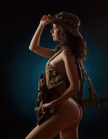 the girl soldier with weapons on black background