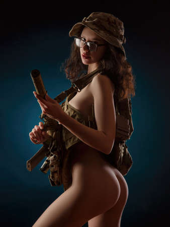 the naked girl soldier with weapons on black background